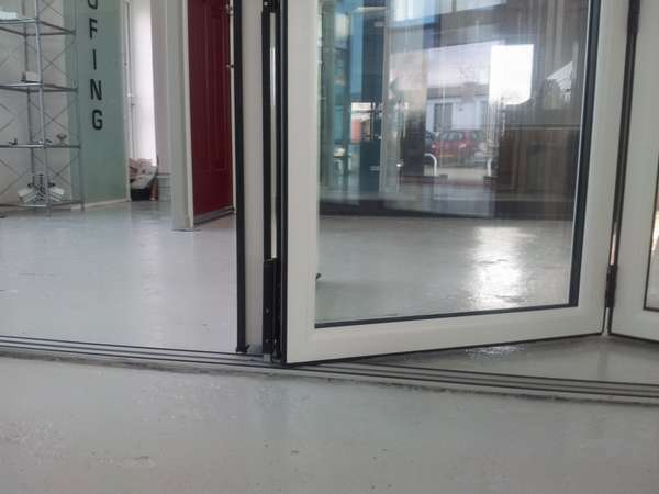 NEW PVCU - AlUMINIUM HYBRID Bi Folding door. Close up photo of Flush floor track