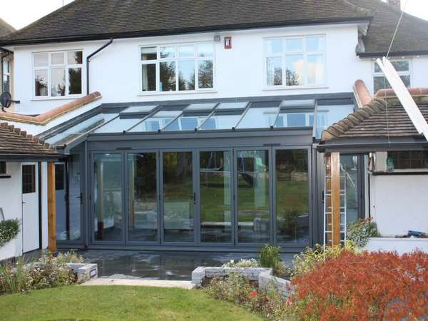 Mrs L: Caldy Wirral: Installation of Centor C1 Aluminium Bi Fold doors , Triple glazed . Marine finish Polyester Powder coated ; Roof K2 Aluminium roof system glazed in Celsius clear