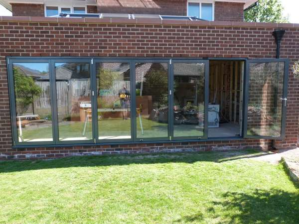 Mr B. Bebington wirral. Installation of 6200mm wide Centor C1 marine finish Alumnium Bi folding door in Ral 7016. The Bi folding doors our triple glazed with 44mm sealed units . The units have an overall U value .6.