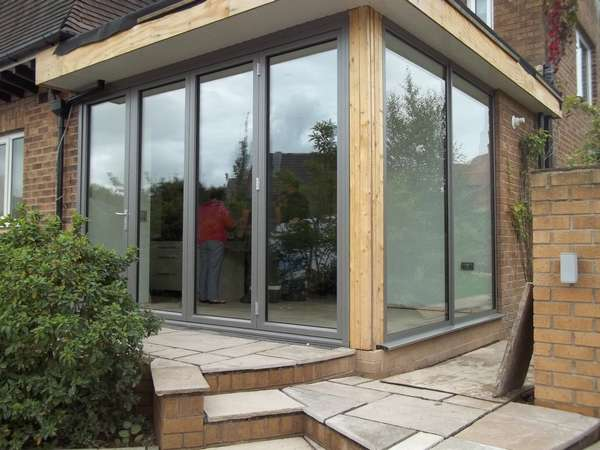 Installtion of Centor C1 Aluminium Bi folding doors with returning fixed window i Hyde Cheshire . The photo is show how the corner after installtion requires matching Aluminium pressing to form a finish . The pressing is the area of the installtion you as